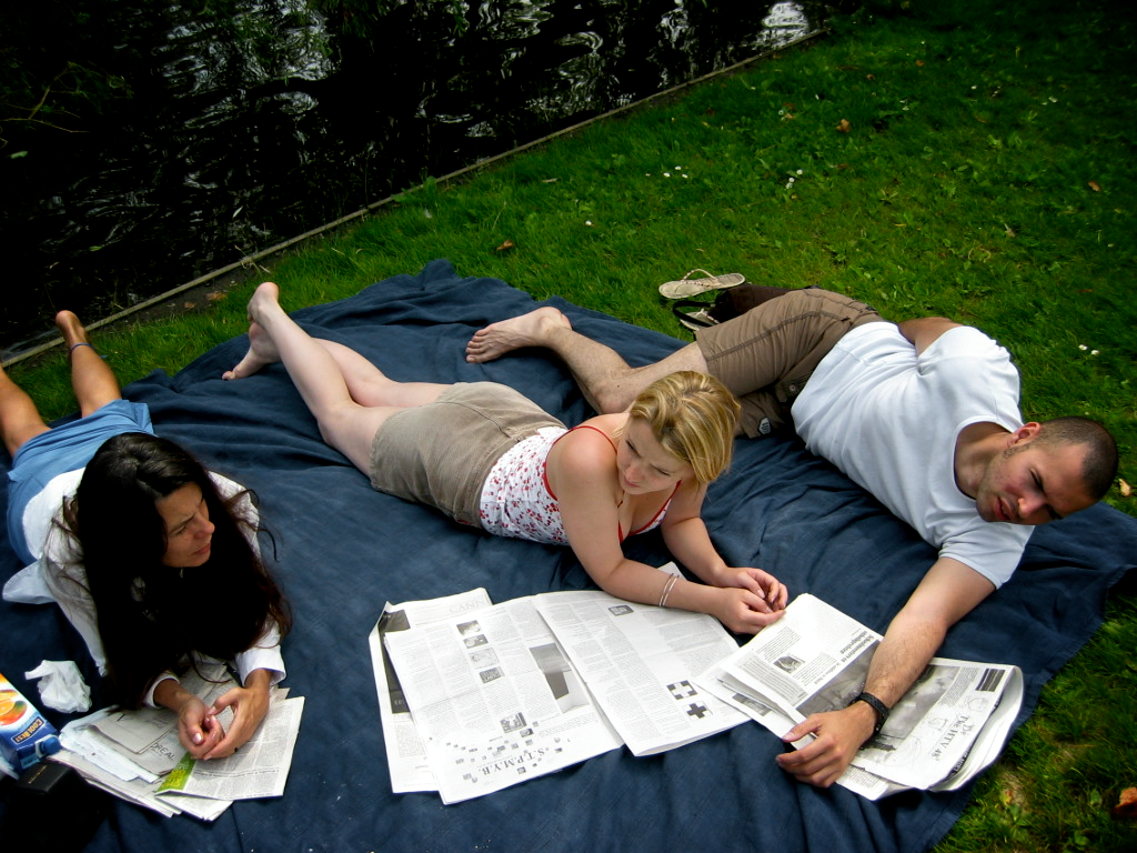 Friends with newspaper at a picnic. Vondelpark, Amsterdam 2003